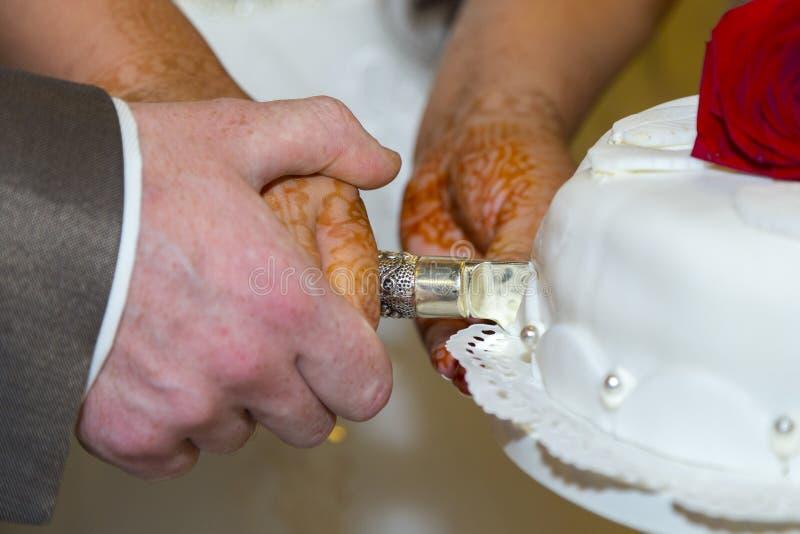 El novio y la novia que cortan el pastel de bodas fotografía de archivo libre de regalías