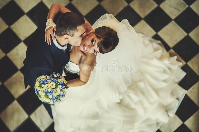 El novio y la novia se está besando en el piso a cuadros del fondo fotografía de archivo libre de regalías