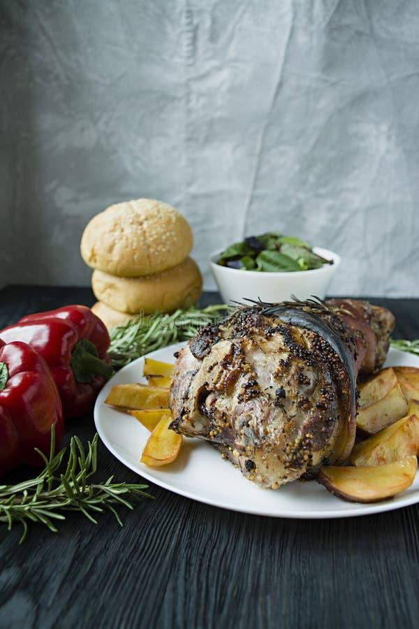 El nudillo frito del cerdo con las patatas sirvi? en una placa blanca Adorn? con la pimienta b?lgara fresca, romero Fondo de made fotografía de archivo