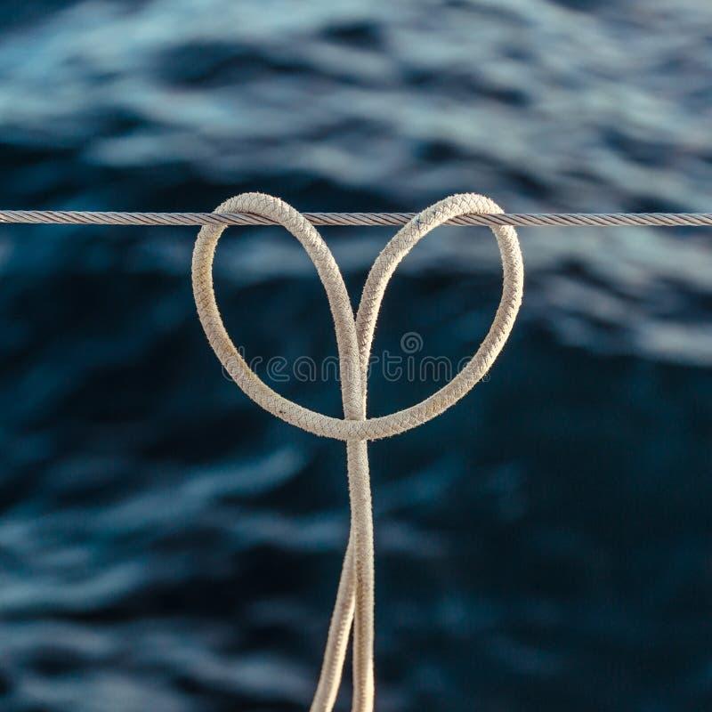 El nudo del tirón del nudo de la cuerda en un cable de acero, en forma de corazón en el fondo del océano fotos de archivo