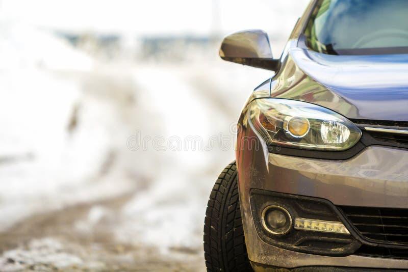 El nuevo coche gris moderno parqueó en una calle en invierno fotos de archivo