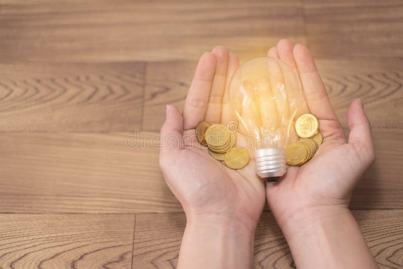 El nuevo concepto de la idea, las mujeres jovenes da sostener la bombilla y monedas en fondos de madera y nuevo poder de la reser foto de archivo libre de regalías