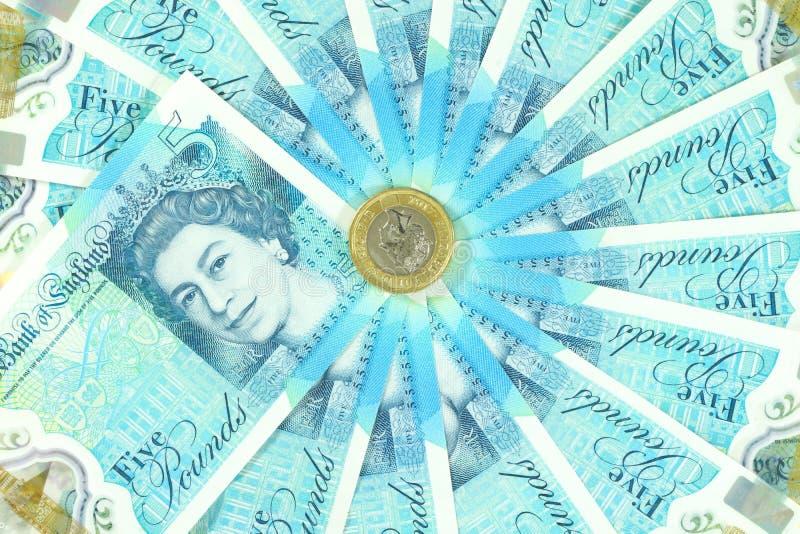 El nuevo polímero BRITÁNICO nota de cinco libras y los nuevos 12 echó a un lado la moneda £1 foto de archivo