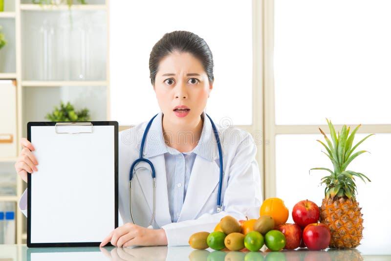 El nutricionista del doctor con las frutas y sostener el tablero en blanco se cayó imagen de archivo libre de regalías