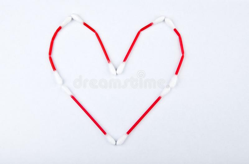 El oído del algodón pega el fondo blanco del símbolo del corazón imagen de archivo