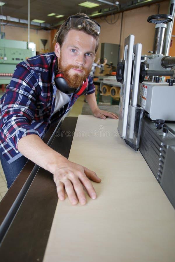 El obrero act?a la cortadora del laser en taller imagenes de archivo