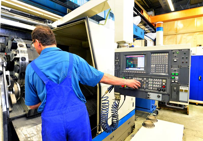 El obrero actúa una fresadora del CNC para la producción imagenes de archivo