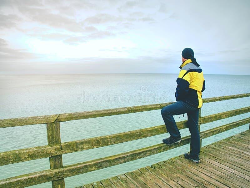 El océano pasa por alto Turista en ropa caliente en topo del mar en la barandilla Turista en el embarcadero en puerto imagenes de archivo