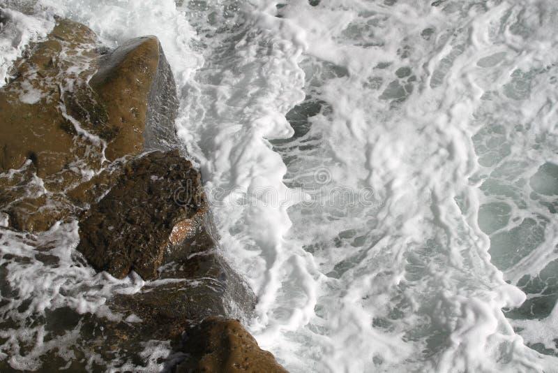 El océano resuelve las rocas en los acantilados imagen de archivo