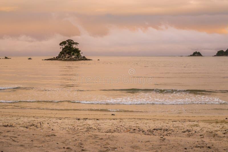 El océano y la playa rosados de la puesta del sol ajardinan, Abel Tasman National Park imágenes de archivo libres de regalías