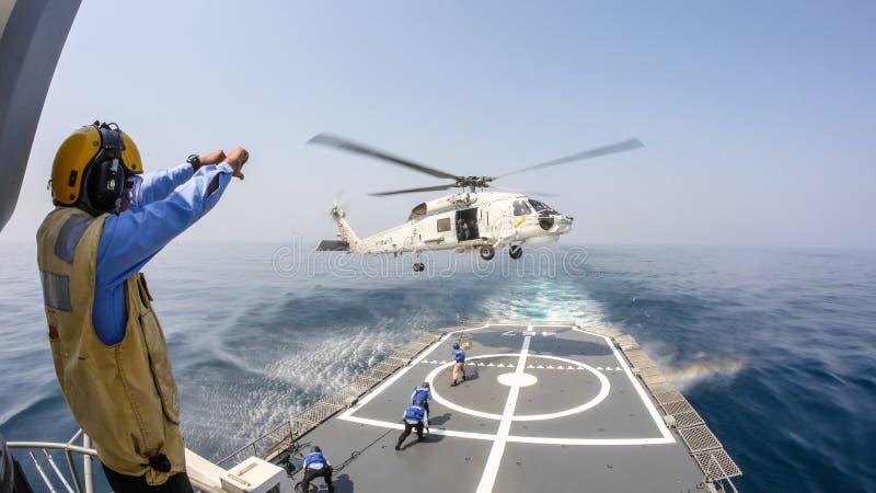 El oficial de la cubierta de helicóptero da la señal de mano al helicóptero del halcón del mar de Sikorsky S-70 que asoma sobre c imágenes de archivo libres de regalías