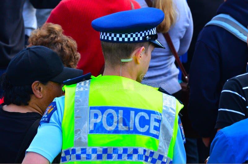 El oficial de policía de Nueva Zelanda camina en cantado de gente fotografía de archivo libre de regalías