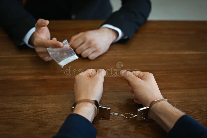 El oficial de policía que interroga al traficante en esposas en el escritorio dentro Criminal imágenes de archivo libres de regalías