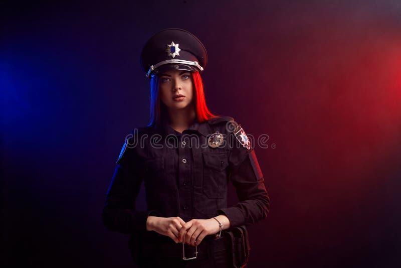El oficial de polic?a de sexo femenino serio est? presentando para la c?mara contra un fondo negro con hacer excursionismo rojo y fotos de archivo libres de regalías