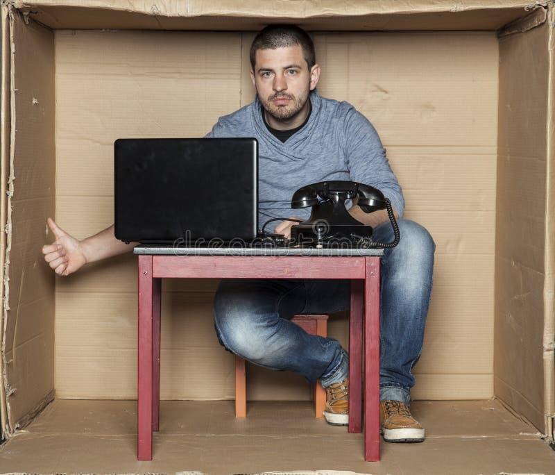El oficinista joven muestra los pulgares para arriba debajo del escritorio fotos de archivo