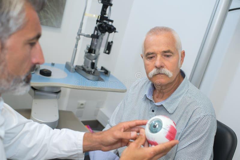 El oftalmólogo muestra viejo problema paciente de la visión imagen de archivo