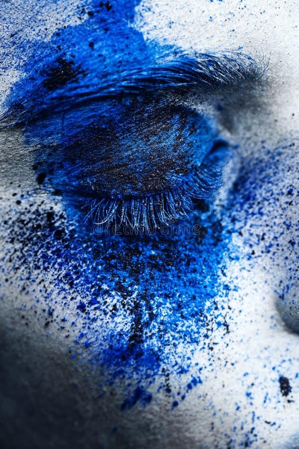 El ojo ascendente del cierre de la muchacha del modelo de moda con el polvo colorido compone fotografía de archivo