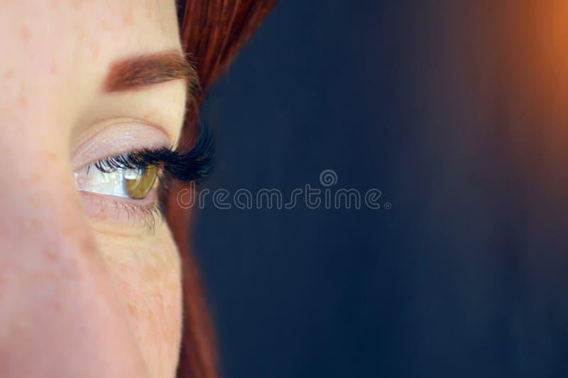 El ojo de la muchacha con el pelo rojo y de ojos verdes con extensiones de la pestaña en un fondo oscuro mira a la izquierda con  imágenes de archivo libres de regalías