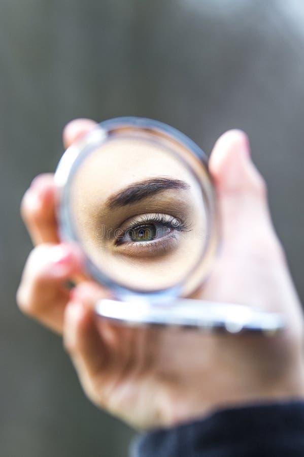 El ojo de la muchacha en espejo compacto imágenes de archivo libres de regalías