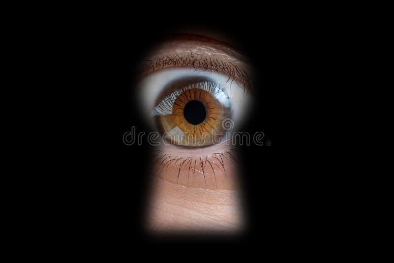 El ojo humano detrás de la puerta está mirando a través de un ojo de la cerradura fotografía de archivo