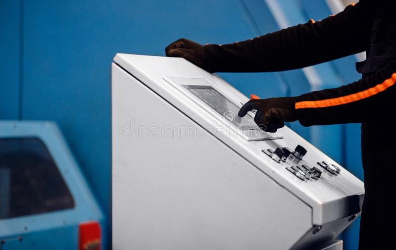 El operador de la producción industrial hace clic en el panel de control de la máquina automática fotos de archivo libres de regalías