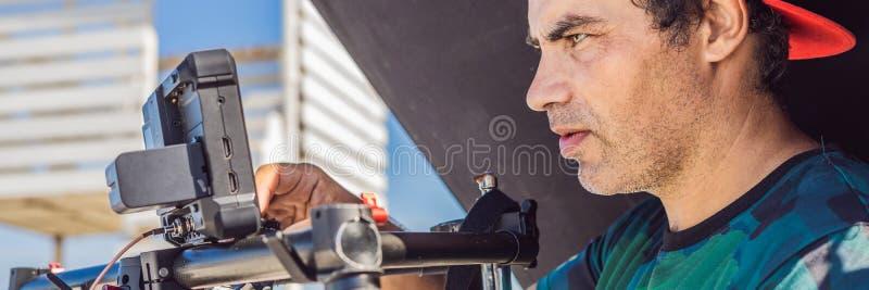 El operador de Steadicam y su ayudante preparan la cámara y el estabilizador-cardán triaxial para una BANDERA comercial del lanza foto de archivo