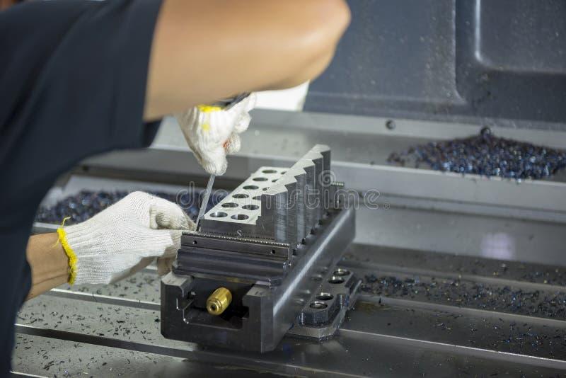 El operador del CNC prepara pedazos del trabajo foto de archivo libre de regalías