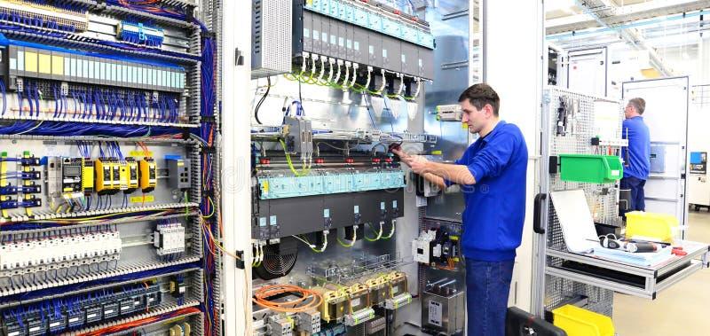 El operador monta la máquina en una fábrica - producción del interruptor c imagen de archivo