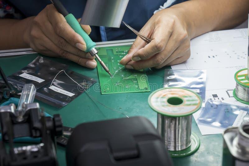 El operador que suelda reparar a la placa de circuito de la electrónica fotografía de archivo