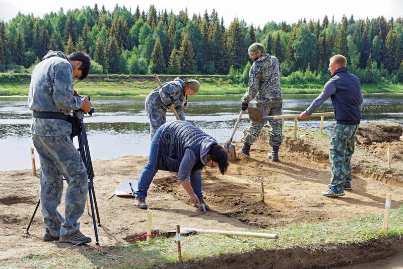 El operador toma un vídeo de un grupo de personas que trabaja en las excavaciones arqueológicas en la orilla del río fotografía de archivo