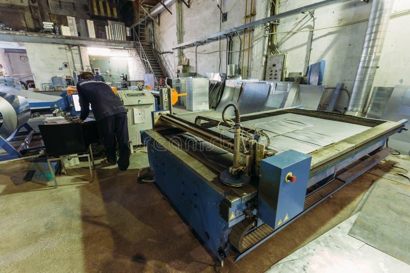 El operador trabaja con la cortadora del plasma con control de programa en fábrica de la trabajo de metalistería fotos de archivo libres de regalías