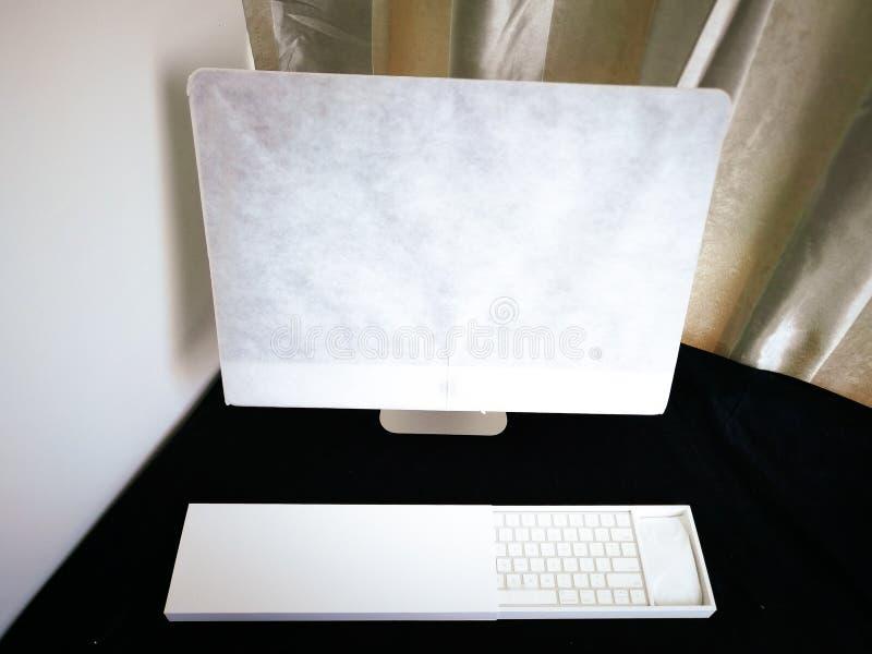 El ordenador comprado en línea todavía se está envolviendo en un escritorio imágenes de archivo libres de regalías
