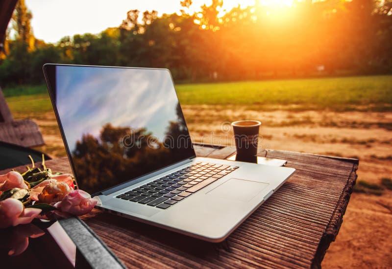 El ordenador portátil en la tabla de madera áspera con la taza de café y el ramo de peonías florece en parque al aire libre foto de archivo