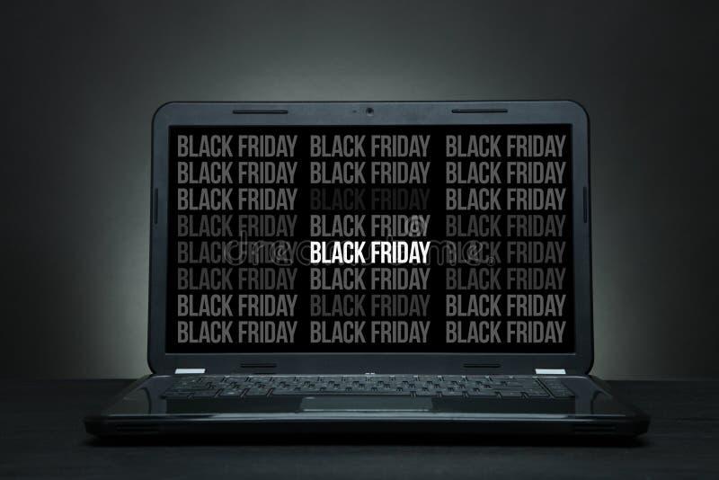 El ordenador portátil está en un escritorio negro fotografía de archivo