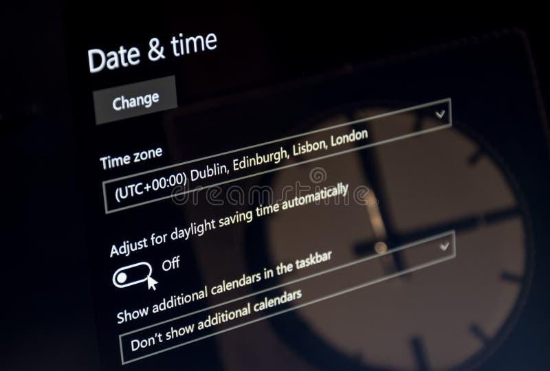 El ordenador portátil que mostraba el menú del tiempo del ahorro del dayligt con un reloj reflejó en la pantalla UTC 00 imágenes de archivo libres de regalías