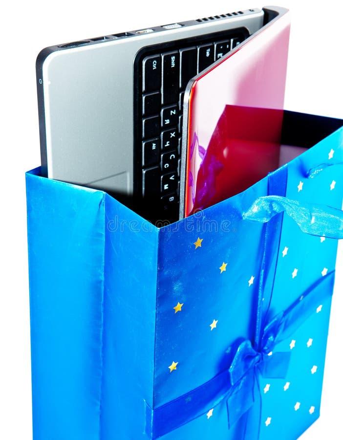 El ordenador portátil rojo se embala en un paquete del regalo imagen de archivo