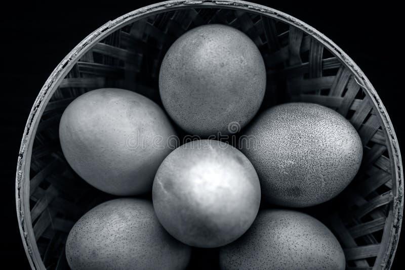 El ` orgánico crudo s de la gallina eggs en una cesta en superficie de madera fotos de archivo