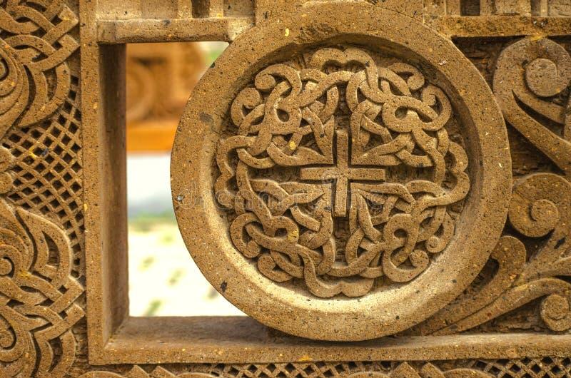 El ornamento del alivio en una piedra volcánica roja, tallada de tiras de intersección con una pequeña cruz en el centro, enmarca imagen de archivo libre de regalías