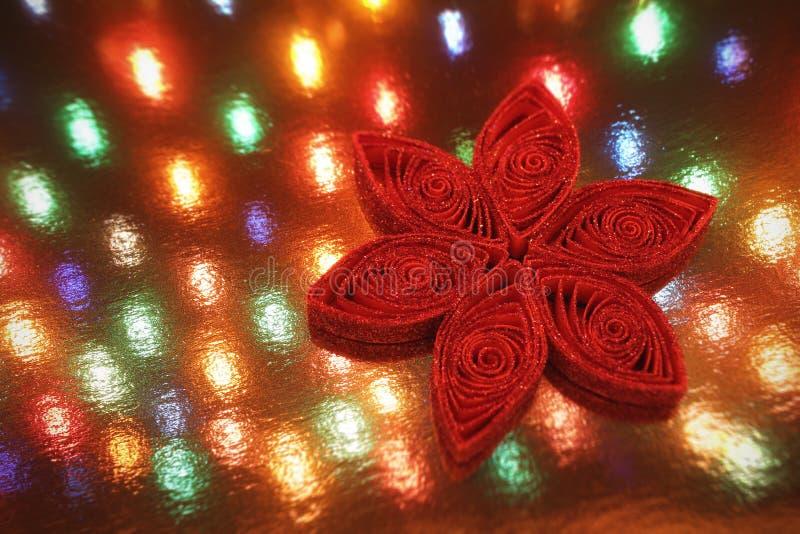 El ornamento rojo de la Navidad del copo de nieve del brillo delante de una guirnalda festiva enciende el fondo fotografía de archivo