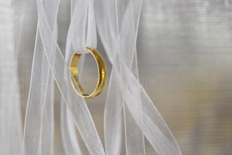 El oro del anillo con la malla blanca de la cinta tiene una ondulación suave, un amor y una conmemoración y un espacio vacío para fotos de archivo libres de regalías