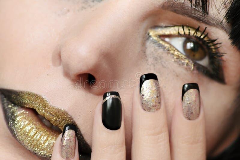 El oro festivo del negro de la moda compone y manicura francesa imagen de archivo libre de regalías