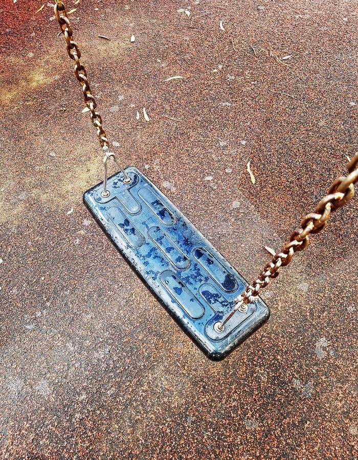 El oscilación de los niños en el parque en el patio imagen de archivo libre de regalías