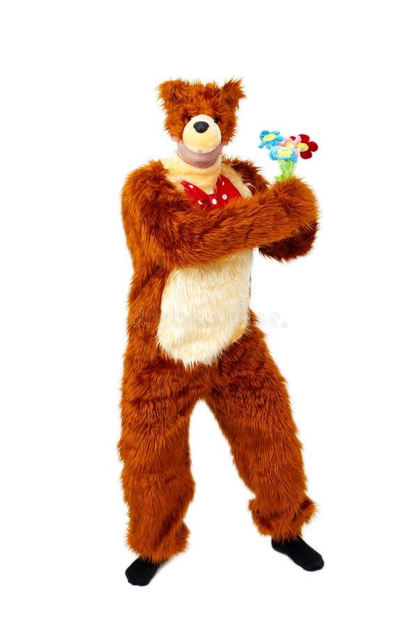 El oso chistoso con el juguete florece en el fondo blanco foto de archivo libre de regalías