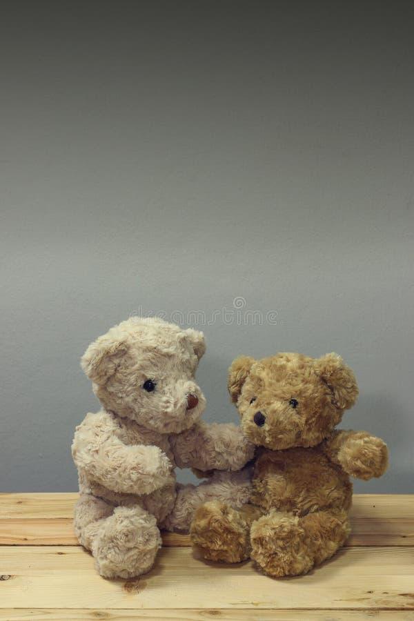 El oso de peluche dos se sienta en la tabla de madera foto de archivo libre de regalías