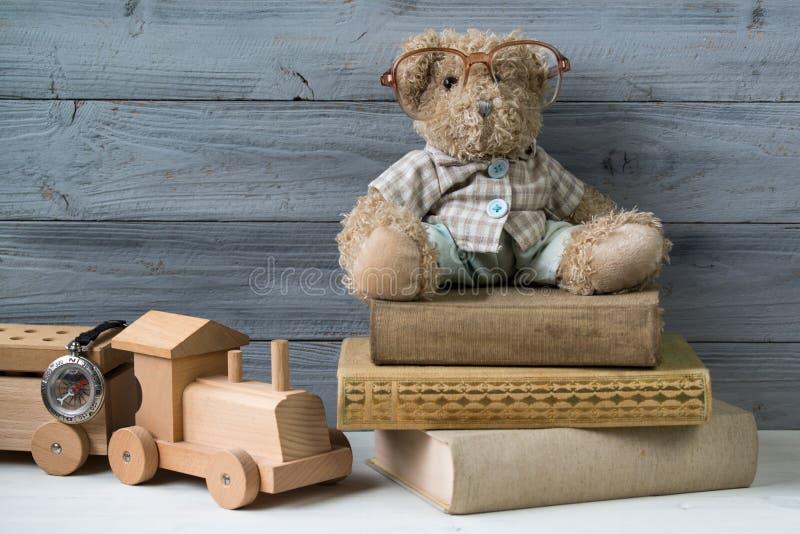 El oso de peluche en vidrios en los libros viejos y el juguete de madera entrenan imágenes de archivo libres de regalías