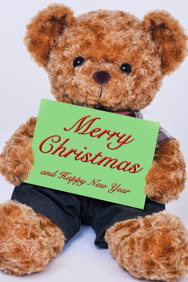 El oso de peluche que lleva a cabo una muestra verde lee Feliz Navidad fotografía de archivo