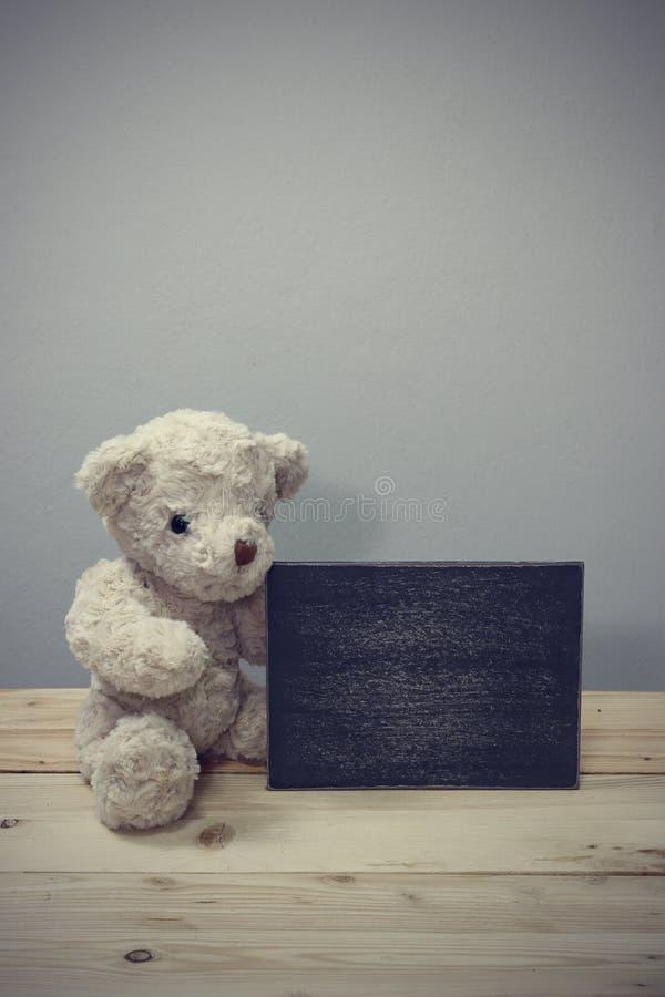 El oso de peluche se sienta en pisos de madera imagen de archivo