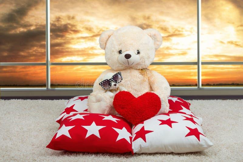 El oso de peluche suave con los vidrios del sol da el corazón, sentándose en la almohada en el fondo de Windows panorámico fotografía de archivo