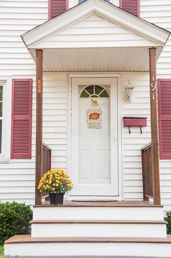 El pórtico de una pequeña casa de madera acogedora y con los crisantemos amarillos en el umbral foto de archivo libre de regalías
