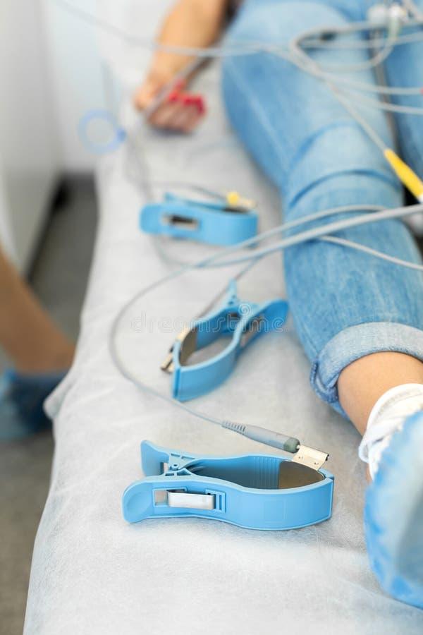 El paciente miente en un sofá al lado de los sensores del electrocardiógrafo Examen médico en la clínica foto de archivo libre de regalías